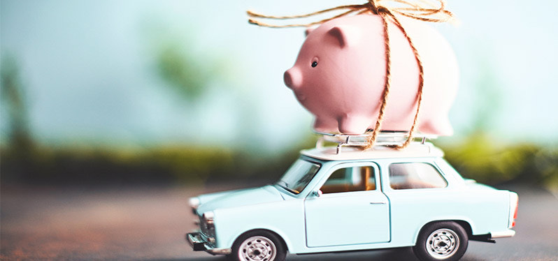 Illustration of a piggy bank strapped to the top of a car