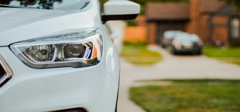 cropped view of a new car parked in a residential driveway