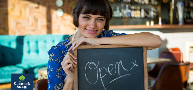 "Woman leaning on an ""Open"" sign"