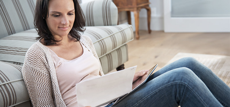 Woman reading while sitting on floor in home
