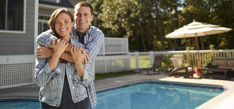 Woman and man standing in front of home pool