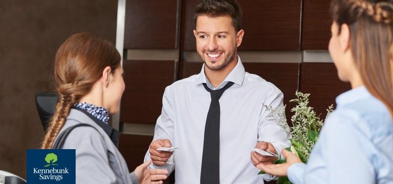 Man handing bank card to two women