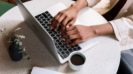 Hands typing on a laptop with a cup of coffee nearby