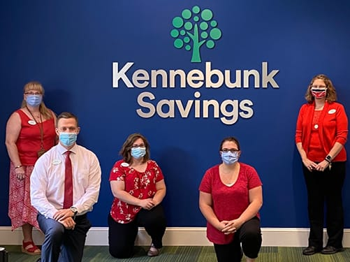 Kennebunk Savings staff by sign