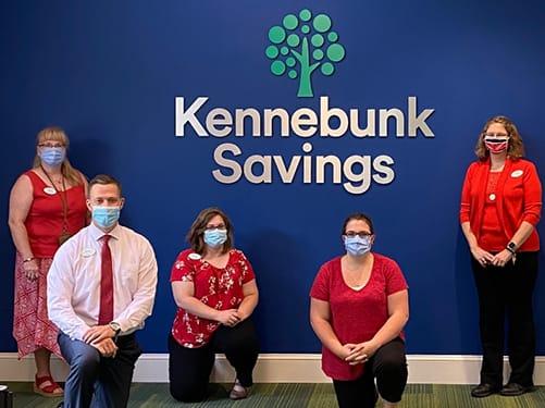 Kennebunk Savings staff by sign