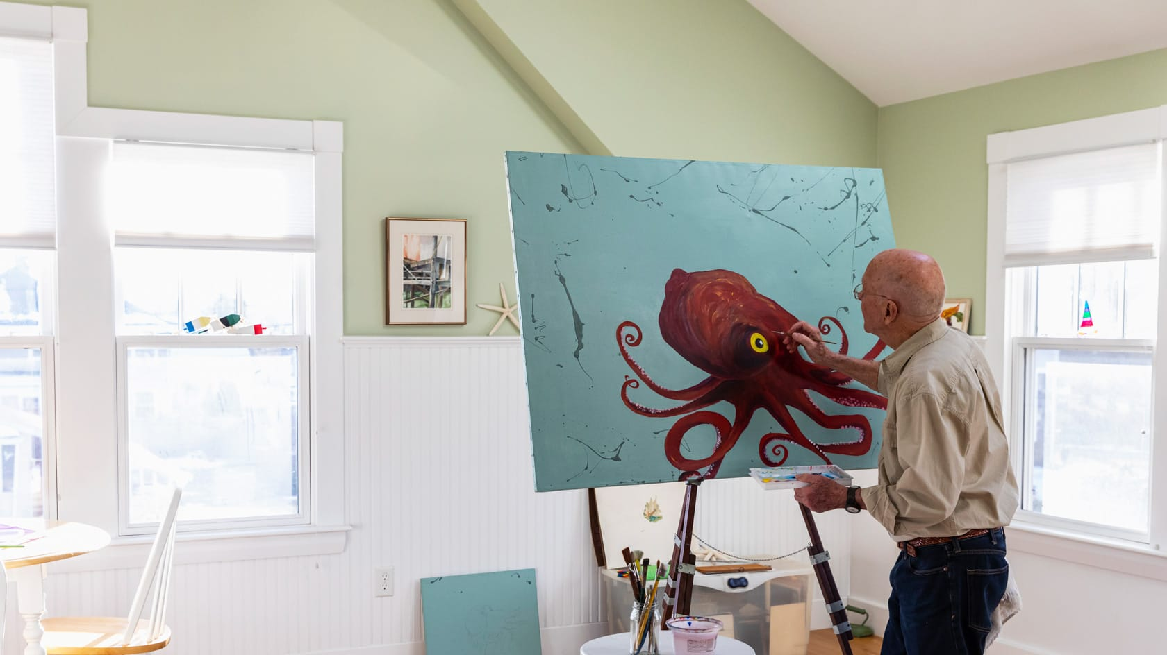 Man painting in octopus in his home