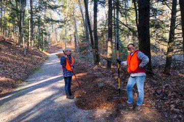 Two staff volunteering to rake leaves