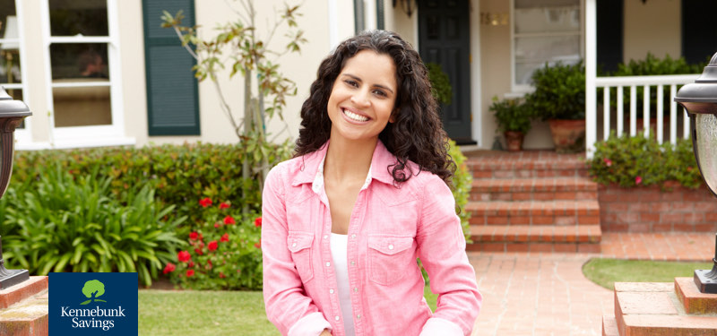 Smiling woman standing in front of home