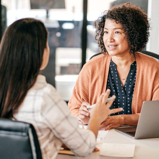 two women talking at a desk
