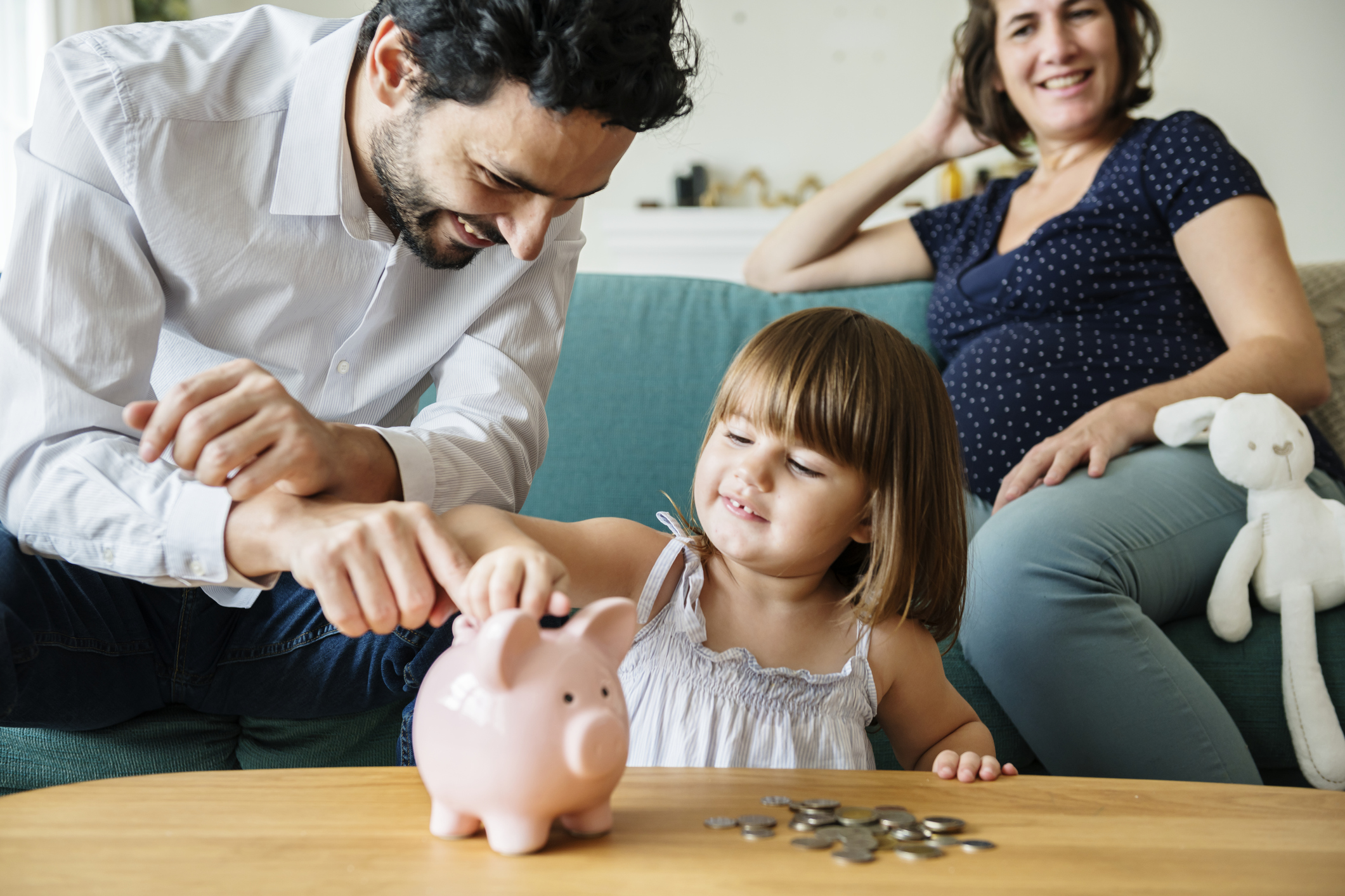 family budgeting on couch, piggy bank, counting money, young girl