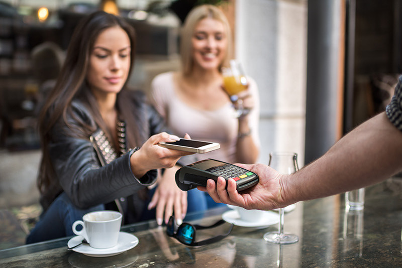 Women using Apple Pay with Checking Accounts on phones
